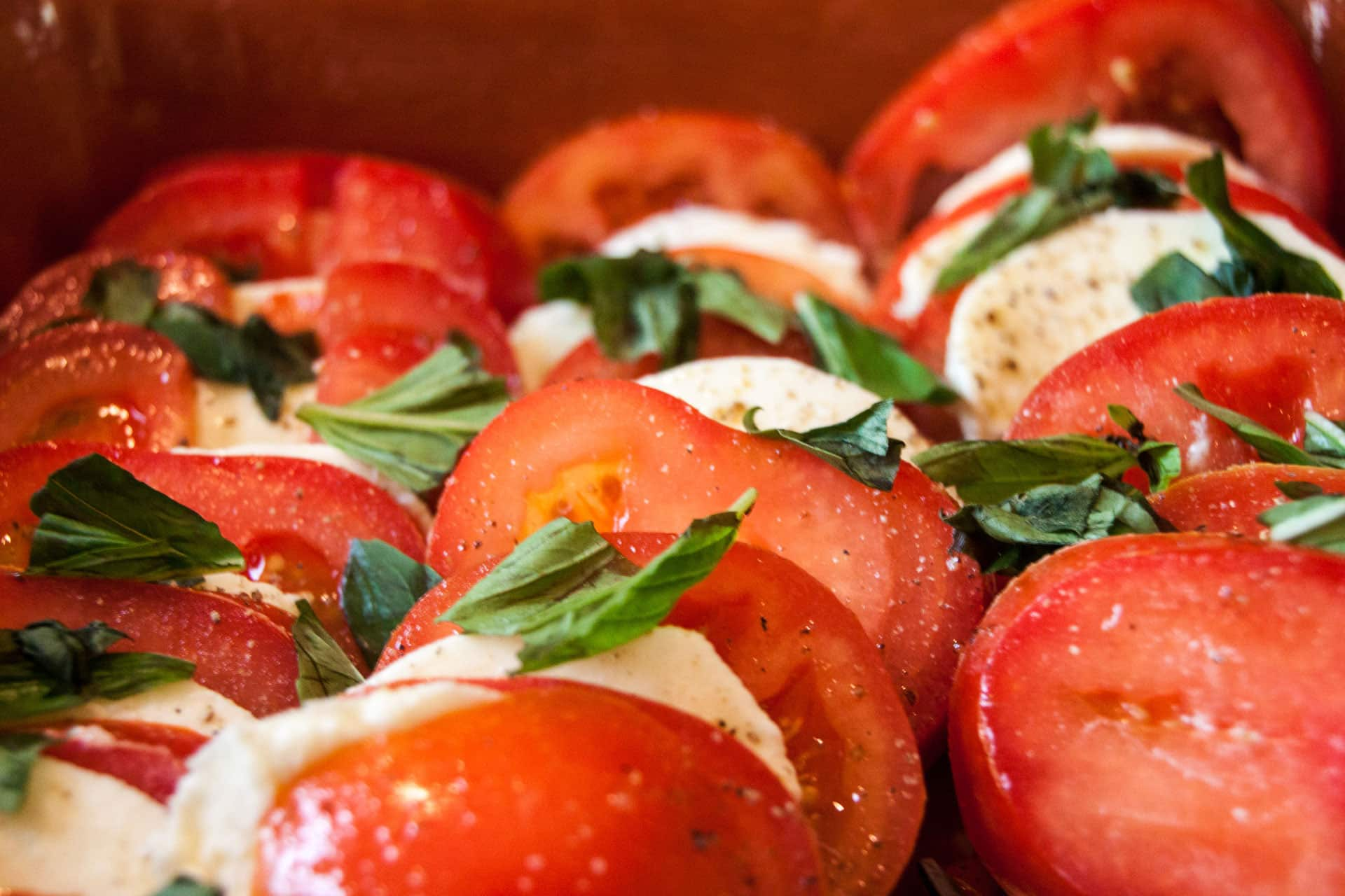 Tomato mozzarella plate with fresh basil and olive oil
